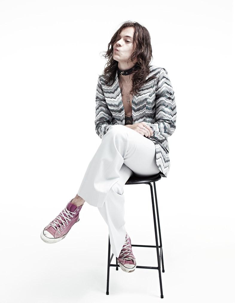 Harry Styles de cabelo comprido, gargantilha, blazer, sem camisa, calça branca e tênis rosa, sentado em um banquinho.