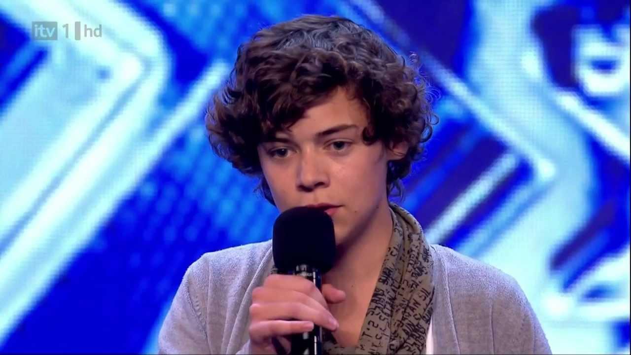 Harry Styles no programa X-Factor, de cabelos cacheados e echarpe.
